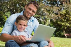 Smiling son and dad with a laptop - stock photo