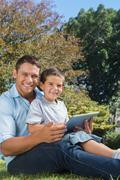 Dad and son with tablet pc smiling into the camera - stock photo