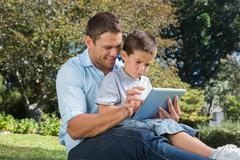 Dad and son using a tablet pc in a park - stock photo