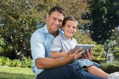 Happy dad and son with a tablet pc - stock photo