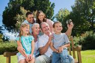 Family sitting on a bench taking photo of themselves Stock Photos