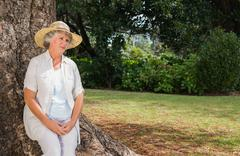 Thoughtful retired woman sitting on tree trunk - stock photo