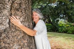 Stock Photo of Smiling older woman hugging a tree