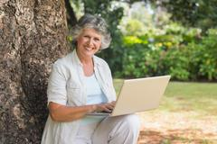 Stock Photo of Mature woman using a laptop sitting on tree trunk