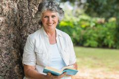 Stock Photo of Cheerful mature woman holding book sitting on tree trunk