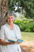 Stock Photo of Smiling mature woman reading book leaning on tree trunk