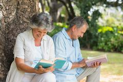 Retired couple reading books together sitting on tree trunk - stock photo