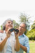 Woman holding binoculars with partner - stock photo