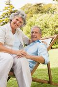 Stock Photo of Smiling mature couple resting on sun lounger
