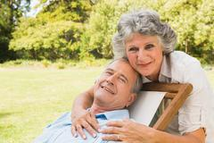 Smiling mature woman standing behind her husband on deck chair - stock photo