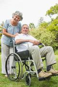 Stock Photo of Smiling mature man in wheelchair with partner