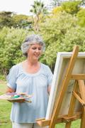 Cheerful mature woman painting on canvas - stock photo