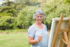 Smiling retired woman painting on canvas - stock photo