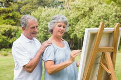 Peaceful retired woman painting on canvas with husband - stock photo