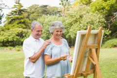 Cheerful retired woman painting on canvas with husband - stock photo