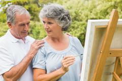 Cheerful retired woman painting on canvas and talking with husband - stock photo