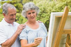 Happy retired woman painting on canvas and talking with husband - stock photo