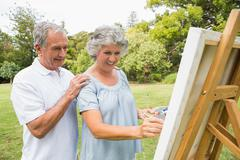 Content retired woman painting on canvas and talking with husband - stock photo