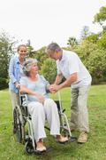 Mature woman in wheelchair with husband and daughter - stock photo
