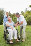 Retired woman in wheelchair with husband and daughter - stock photo