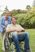 Stock Photo of Happy man in wheelchair with partner