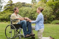 Content man in wheelchair with partner kneeling beside him Stock Photos