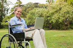 Smiling woman in a wheelchair with a laptop - stock photo