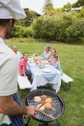 Stock Photo of Happy extended family having a barbecue being cooked by father in chefs hat
