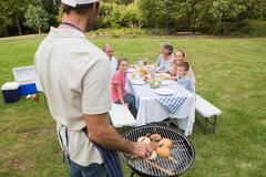 Stock Photo of Father in chefs hat and apron cooking barbecue for his family