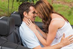 Young couple feeling romantic in back seat - stock photo