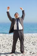 Victorious businessman in suit holding arms up - stock photo