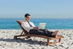 Young businessman lying on a deck chair with his laptop - stock photo