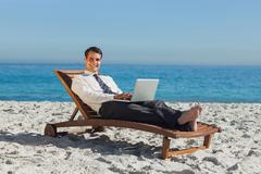 Smiling young businessman lying on a deck chair with his laptop Stock Photos