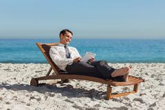 Young businessman relaxing on a deck chair using his tablet - stock photo