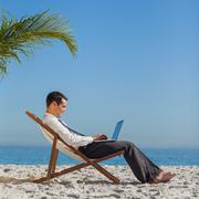 Young businessman on his beach chair using his laptop Stock Photos
