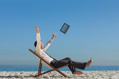 Victorious young businessman on his deck chair throwing his tablet away Stock Photos