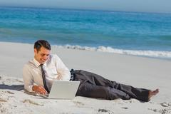 Cheerful young businessman lying on the sand with his laptop Stock Photos