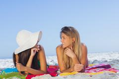 Two pretty women lying on the sand - stock photo