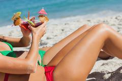Sexy women taking sun clinking cocktails Stock Photos