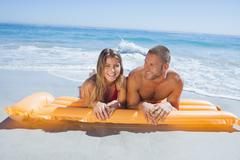 Stock Photo of Cheerful cute couple in swimsuit lying on the beach
