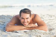 Smiling handsome man on the beach lying on his towel - stock photo