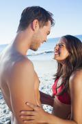 Stock Photo of Cheerful cute couple in swimsuit holding one another