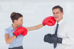 Businesswoman punching her colleague while boxing together - stock photo