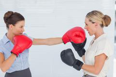 Brown haired businesswoman punching her blond colleague during boxing match - stock photo
