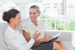 Smiling businesswomen talking and working together - stock photo