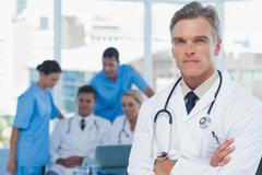 Stock Photo of Experienced doctor posing with colleagues in background