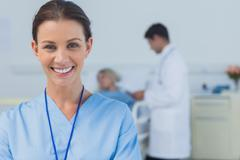 Stock Photo of Cheerful surgeon posing with doctor attending patient on background