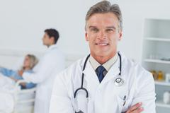 Stock Photo of Experienced doctor posing with doctor attending patient on background