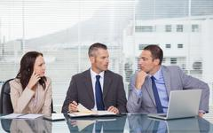 Serious business people talking together while waiting for interview - stock photo
