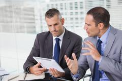 Serious businessmen analyzing documents on their tablet - stock photo